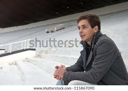 the guy sitting in the stands and looking the game