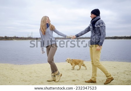 the guy, the girl and dog walk on a sandy beach