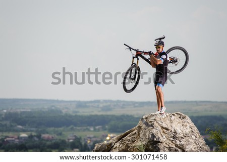the guy with the bike on top of the mountain carry his bicycle - stock photo