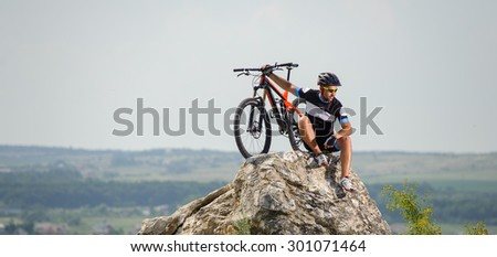 the guy with the bike on top of the mountain sitting on the rock - stock photo