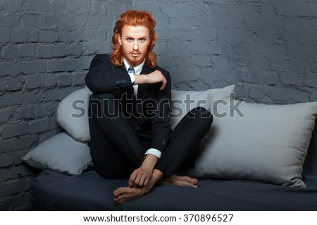 The guy with the red hair and beard, sitting on the sofa. Freckles on his face.