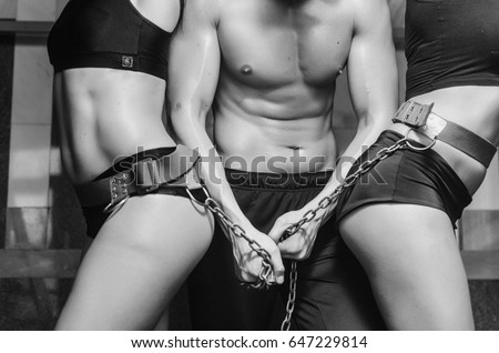 The gym on the background of trainers. People do sports to keep a slender figure. the guy with the chains, the girls holding the chain. body parts close up, such as the abdomen, back muscles.