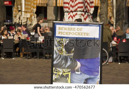 The Hague, Holland - March 12, 2016: Sign with a warning against pickpockets and people sitting in outdoor cafe on the Plein townsquare in The Hague, Holland on March 12, 2016