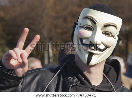 THE HAGUE – OCTOBER 15: Masked member of Anonymous making victory hand sign during the Occupy protest on October 15, 2011 in The Hague, The Netherlands.