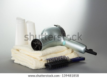 The hair dryer for hair, a hairbrush and toilet accessories on a gray background - stock photo