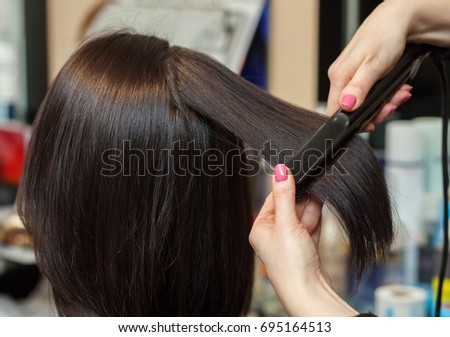 The hairdresser does aligns the hair with hair iron to a young girl, brunette in a beauty salon. Professional Hair Care