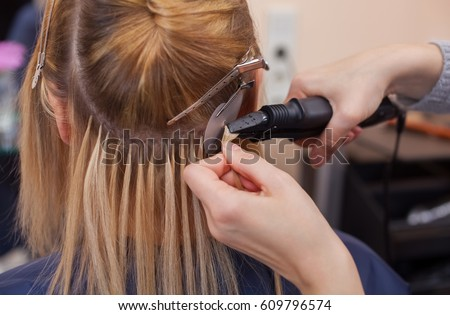 Hair extensions stock images royalty free images vectors the hairdresser does hair extensions to a young girl a blonde in a beauty salon pmusecretfo Choice Image