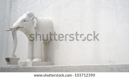 The half of elephant in the white wall of asian temple