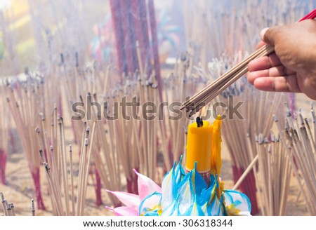 the hand and the fire candle and the burning joss stick , burnig candle  and burning  incense  - stock photo