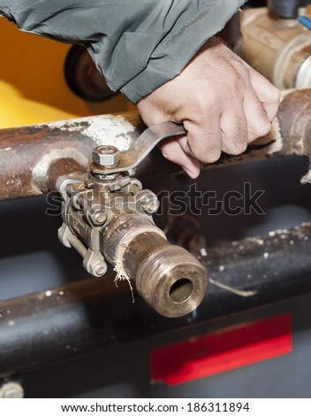 The hand closes the crane (ball valve) - stock photo