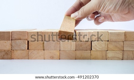 The hand establishes a wooden cube in row. on a white background