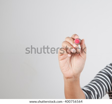 the hand holds a bright red lipstick - stock photo