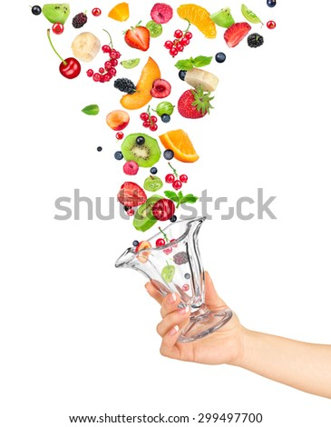 the hand holds the glass bowl of fruit salad and the ingredients in the air isolated on white background - stock photo