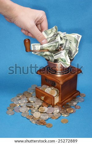 The hand mills dollars in a coffee grinder - stock photo