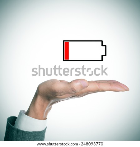 the hand of a businessman holding an illustration of a low battery - stock photo