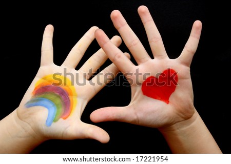 The hand of a child painted with rainbow and red heart - stock photo