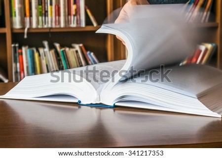 The hand of a man opening and browsing the book pages