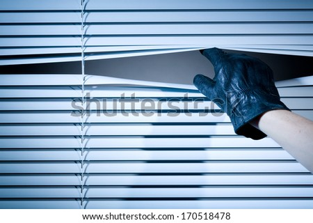 The hand of a thief wearing a leather glove peeking through a window with closed venetian blinds.