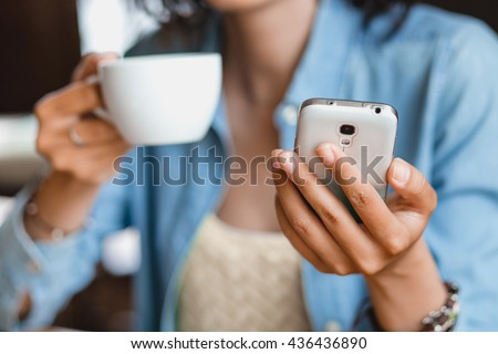 the hand of a woman with a phone and a mug of tea in the cafe