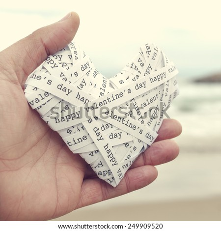 the hand of a young man holding a heart made-up with paper strips with the text happy valentines day, with a filter effect - stock photo