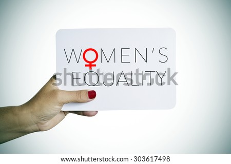 the hand of a young woman holding a signboard with the text womens equality written in it - stock photo