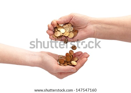 The hand of an elderly woman pouring coins into the hand of a young female. Isolated over white. - stock photo