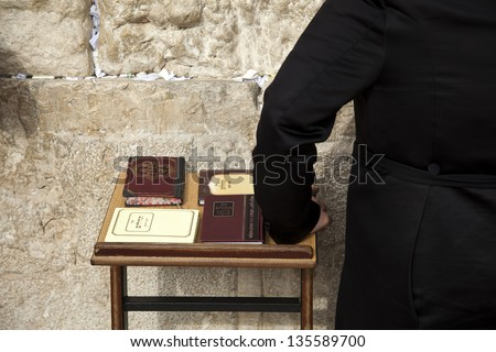 The hand of an orthodox Jewish man resting on a pedestal with four editions of the biblical book of psalms. Shot at the wailing wall in the old city of Jerusalem, Israel. - stock photo