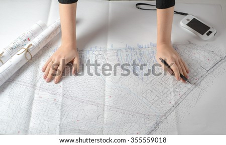 The hand of engineer woman with a pencil on the drawing