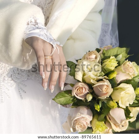 the hand of fiancee lies on a bouquet from roses