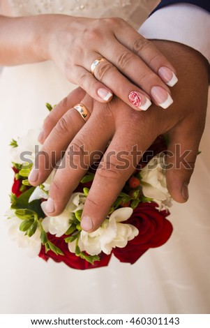 the hand of the bride and groom with wedding rings lie on a bouquet of roses