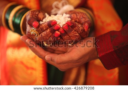 The hand of the bride held by a groom during a traditional ritual in an Indian Hindu Wedding