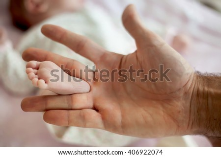 the hand of the father holds a leg of the newborn daughter - stock photo