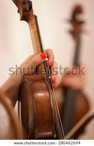 The hand of the girl holding the violin in the orchestra closeup - stock photo