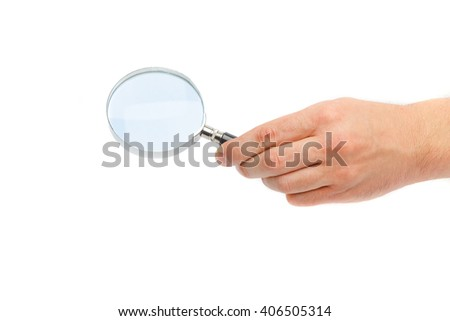 The hand of the man holds a magnifying glass. A magnifying glass in a hand on a white background. - stock photo