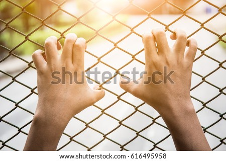 The hand of the man who carved a steel cage in detention of the accused/concept, imprisoned and freedom.