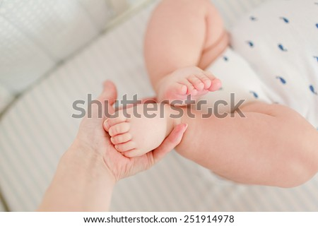 The hand of the mother holds her plump legs baby, close up - stock photo
