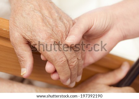 The hand of the old man and his daughter in the fifties, next to the hospital bed. Blur the edges. Focus on an old hand.  - stock photo