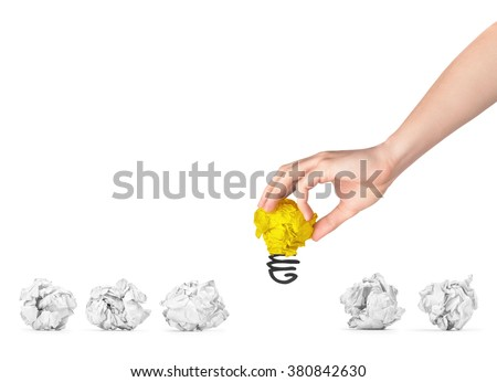 The hand picked bright crumpled paper out of some simple crumpled papers. The concept of selecting the best ideas. - stock photo
