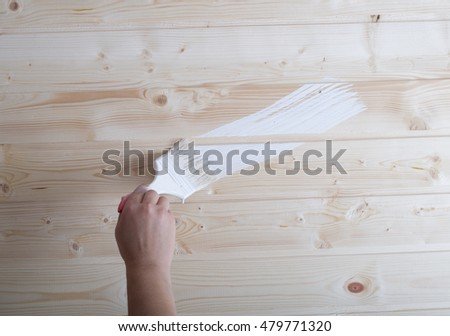 The hand with a brush paints a wooden wall in white