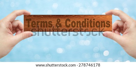 The Hands holding a wood engrave with word Terms & Conditions  with bokeh background - stock photo