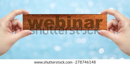 The Hands holding a wood engrave with word webinar with bokeh background - stock photo