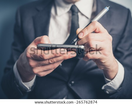 The hands of a businessman as he is using an electronic pen on his smartphone