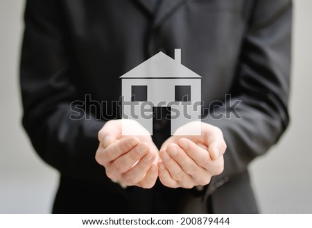 the hands of a man holding a house - insurance, security and protection concept - stock photo
