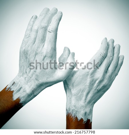 the hands of a man painted in white forming a dove of peace - stock photo