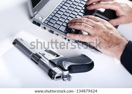 The hands of a mature adult man are in the middle typing and a 9mm handgun by his side. - stock photo