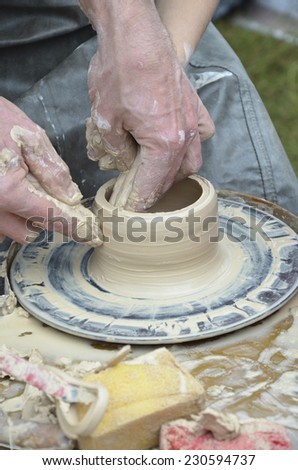 The hands of a potter, creating an earthen pot on a pottery wheel