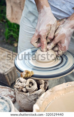 The hands of a potter help the child make a pitcher on a pottery wheel - stock photo