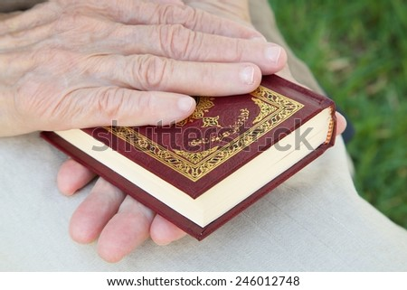 The hands of a senior woman on the Koran - stock photo