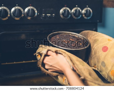 The hands of a woman is removing a burnt cake from the oven