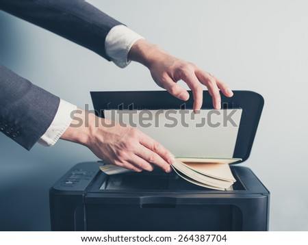 The hands of a young businessman is placing a book on a flatbed scanner in preparation for copying it